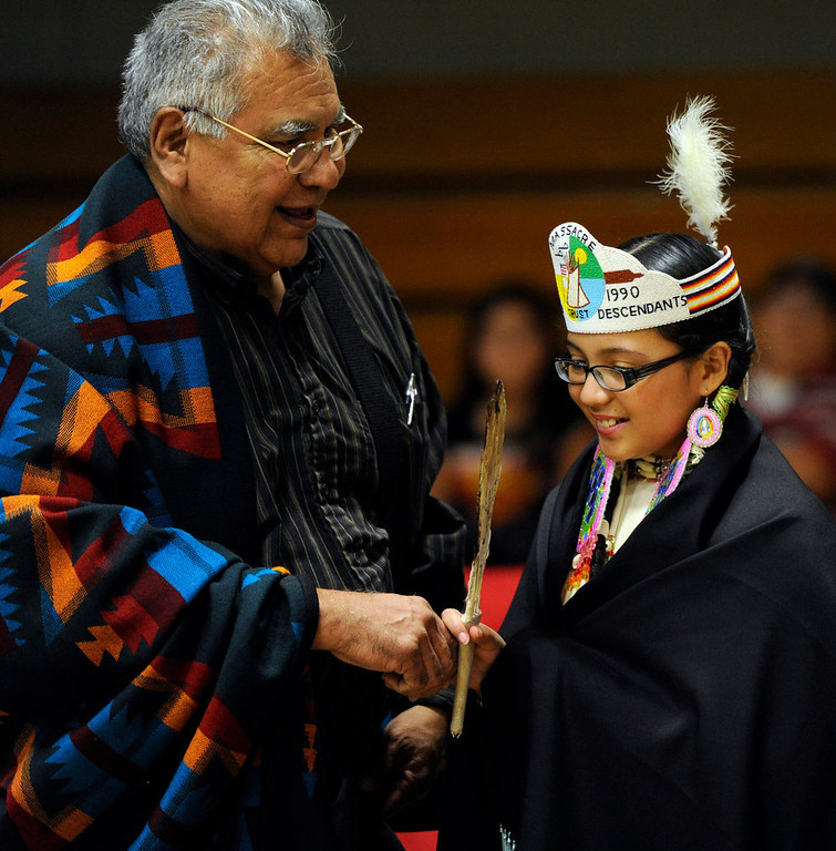. Robert Simpson, congratulates his granddaughter, Samantha Wells, 11-years-old, after becoming the newly crowned Sand Creek Massacre Descendants Trust Princess during a ceremony at the 22nd annual Sand Creek Descendants Gathering in Anadarko Oklahoma, Saturday, December 1st, 2012. Nearly 100 descendants of the Sand Creek Massacre gathered at the Anadarko High School gym for traditional Gourd dancing, food and other activities and also to get updates on legal action towards the U.S. for the massacre which left over 150 Cheyenne and Arapaho Indians dead in southeast Colorado November 29th, 1864. Chief White Antelope, who was killed in the Sand Creek Massacre, is Simpson\'s great great grandfather. The Denver Post/ Andy Cross