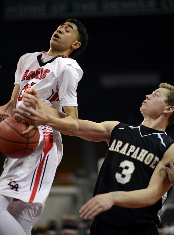 . DENVER, CO. - MARCH 08: Ronnie Harrell #25 of East High School, left, controls the rebound against Ethan Brunhofer #3 of Arapahoe High School during 5A state quarter final game at Denver Coliseum. March 8, 2013. Denver, Colorado. (Photo By Hyoung Chang/The Denver Post)