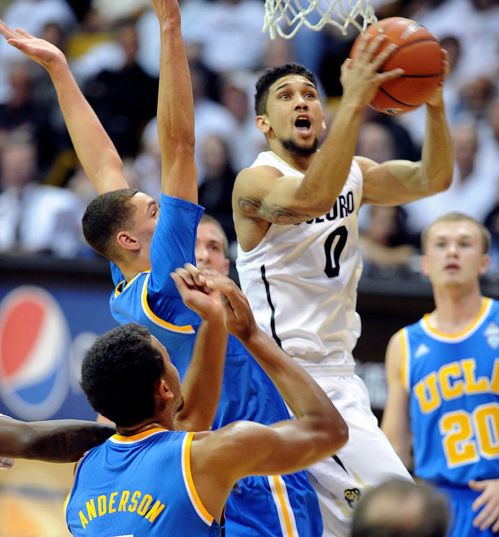 . Askia Booker  of CU drives on the UCLA defense during the second half of the January 16, 2014 game in Boulder.  (Cliff Grassmick/Daily Camera)