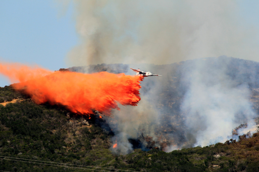 . A plane drops fire retardant in the area of Harmony Grove in Escondido, Calif., Thursday, May 15, 2014. One of nine fires burning in San Diego County, California, suddenly roared Thursday afternoon, moving closer to homes. (AP Photo/U-T San Diego, Howard Lipin)