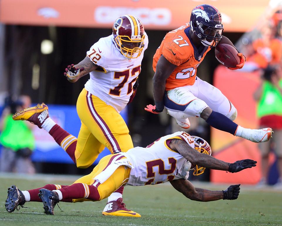 . Denver Broncos running back Knowshon Moreno (27) jumps over Washington Redskins cornerback DeAngelo Hall (23) in the third quarter.   (Photo by AAron Ontiveroz/The Denver Post)