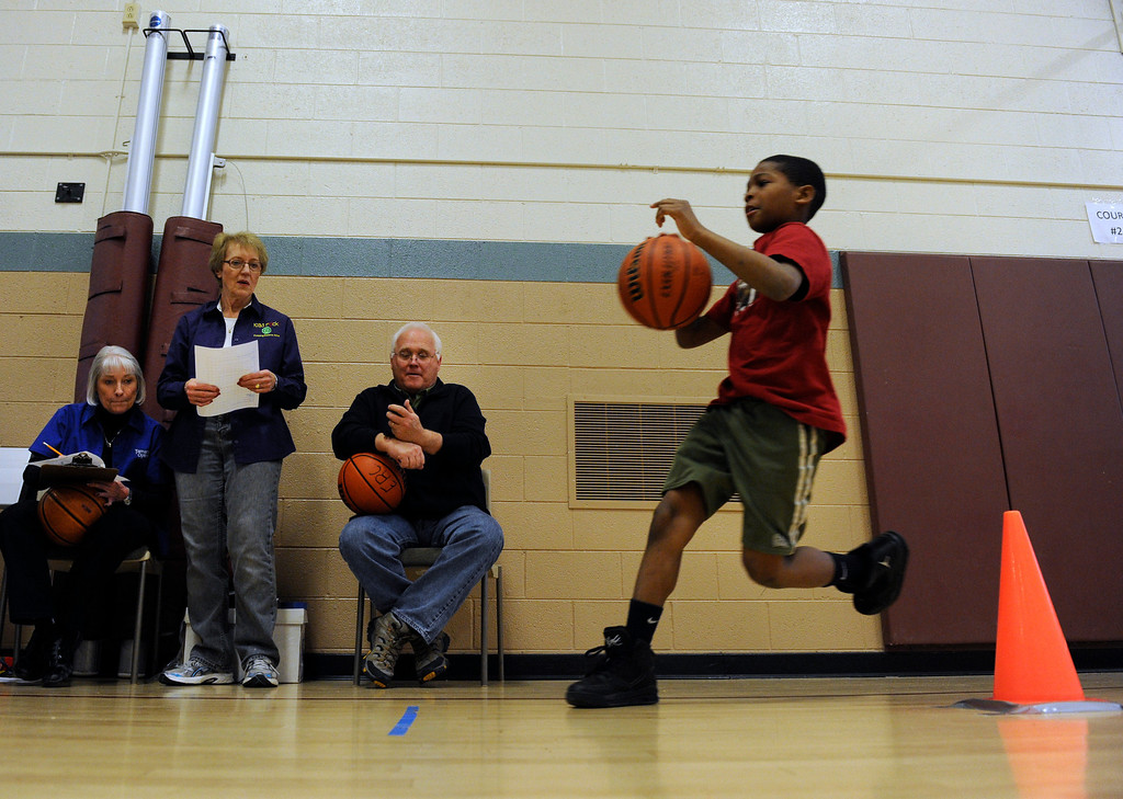 . DENVER, CO. - FEBRUARY 23: Volunteers mark the time of Kenyel Anderson, 8 as he makes his way past the last cone in the dribbling skill test. The Tamarac Optimist Club sponsors one of the Tri-Star Basketball Competitions at the Eisenhower Recreation Center in Denver. The competitions are held over a several week period for boys and girls 8-13 years-old. The winners from this competition go on to the regional finals, and those winners will play in the final competition on Mar. 23, 2013 at the Pepsi Center before a Nuggets game. There are still several opportunities for kids to try out. Go to www.tristarbasketball.org for upcoming times and locations. (Photo By Kathryn Scott Osler/The Denver Post)