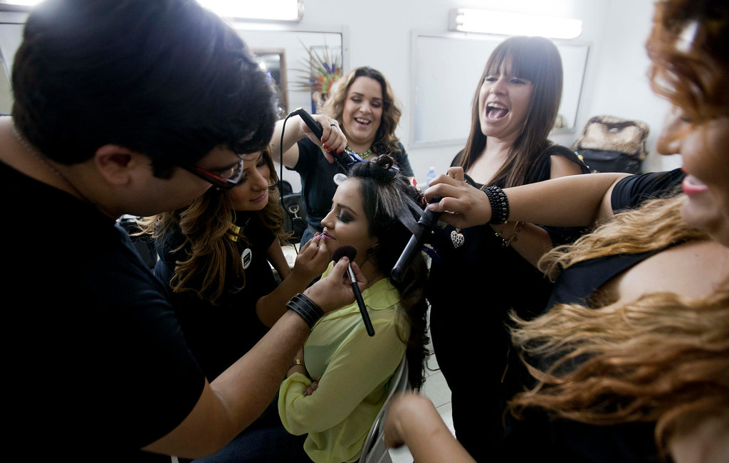 """. In this Jan. 26, 2013 photo, Magdabelyn Parra Gamez, who goes by Belyn, holds still for her make-up backstage before competing in the \""""Guamuchil Carnival Queen 2013\"""" beauty pageant in Guamuchil, Sinaloa state, Mexico.  Belyn, 18, took up the mantle on the pageant circuit after the death of her cousin beauty queen Maria Susana Flores Gamez, who in November 2012 died like a mobster\'s moll, carrying an AK-47 assault rifle into a spray of gunfire from Mexican soldiers. \""""This is in memory of Susy,\"""" Belyn whispered, shortly before winning the crown, \""""In honor of her.\"""" (AP Photo/Eduardo Verdugo)"""