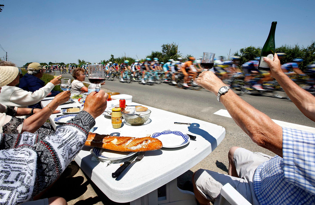 . Spectators eat a picnic lunch as the pack of riders cycles on its way during the twelfth 218km stage of the centenary Tour de France cycling race from Fougeres to Tours July 11, 2013.    REUTERS/Eric Gaillard