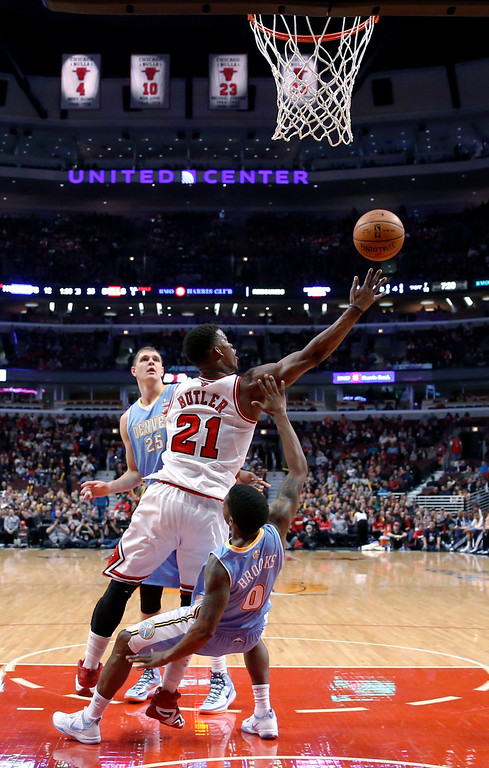 . Chicago Bulls shooting guard Jimmy Butler (21) scores on a shot over Denver Nuggets point guard Aaron Brooks as Timofey Mozgov (25) watches during the first half of an NBA basketball game Friday, Feb. 21, 2014, in Chicago. (AP Photo/Charles Rex Arbogast)