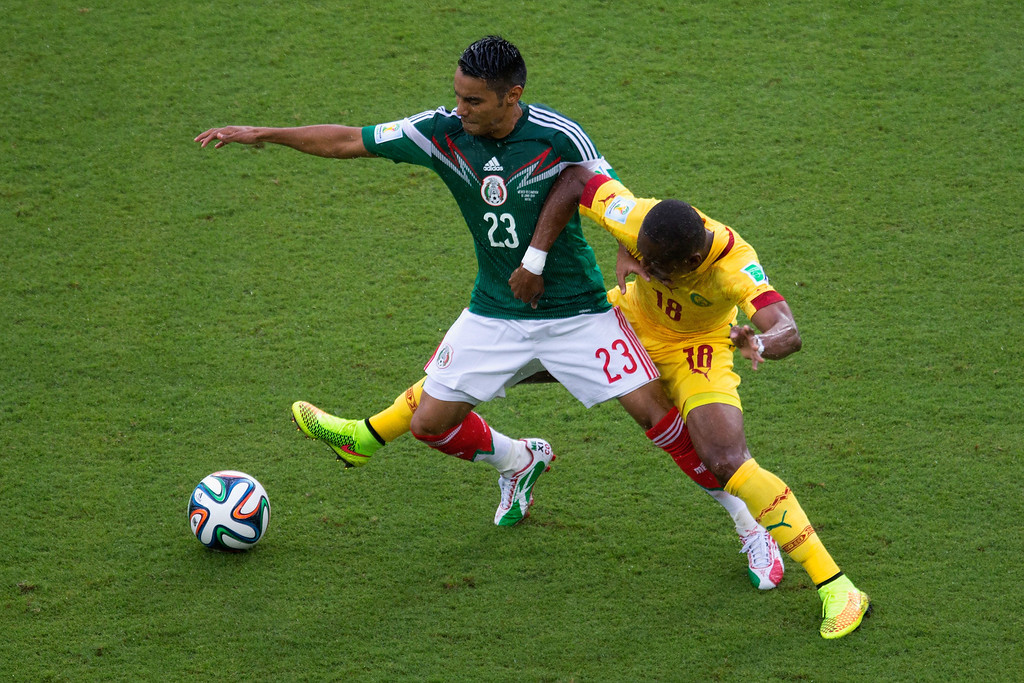 . Enoh Eyong of Cameroon challenges Jose Juan Vazquez of Mexico in the first half during the 2014 FIFA World Cup Brazil Group A match between Mexico and Cameroon at Estadio das Dunas on June 13, 2014 in Natal, Brazil.  (Photo by Miguel Tovar/Getty Images)