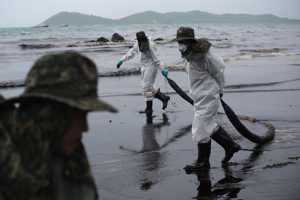 . Royal Thai Navy personnel clean up a beach from a major oil slick on Ao Phrao beach on the island of Ko Samet on July 30, 2013. Thai navy personnel battled to clean up the major oil slick which coated a beach on the popular tourist island in a national park after a pipeline leak.   NICOLAS ASFOURI/AFP/Getty Images