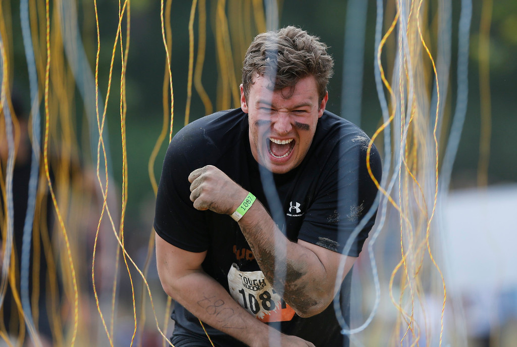 """. A participant of the \""""Tough Mudder\"""" endurance event series reacts as he runs through the \""""Electroshock Therapy\"""" obstacle made of electrical wires holding some 10,000 Volts in the Fursten Forest, a former British Army training ground near the north-western German city of Osnabrueck July 13, 2013. The hardcore but un-timed event over 16 km (12 miles) was designed by British Special Forces to test mental as well as physical strength. Some 4,000 competitors had to overcome obstacles of common human fears, such as fire, water, electricity and heights.   REUTERS/Wolfgang Rattay"""