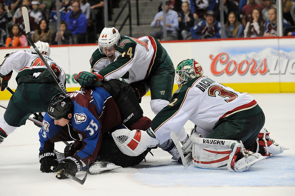 . Justin Falk (44) of the Minnesota Wild shoves Cody McLeod (55) of the Colorado Avalanche out of the crease during the third period, Saturday, April 27, 2012 at Pepsi Center. Seth A. McConnell, The Denver Post