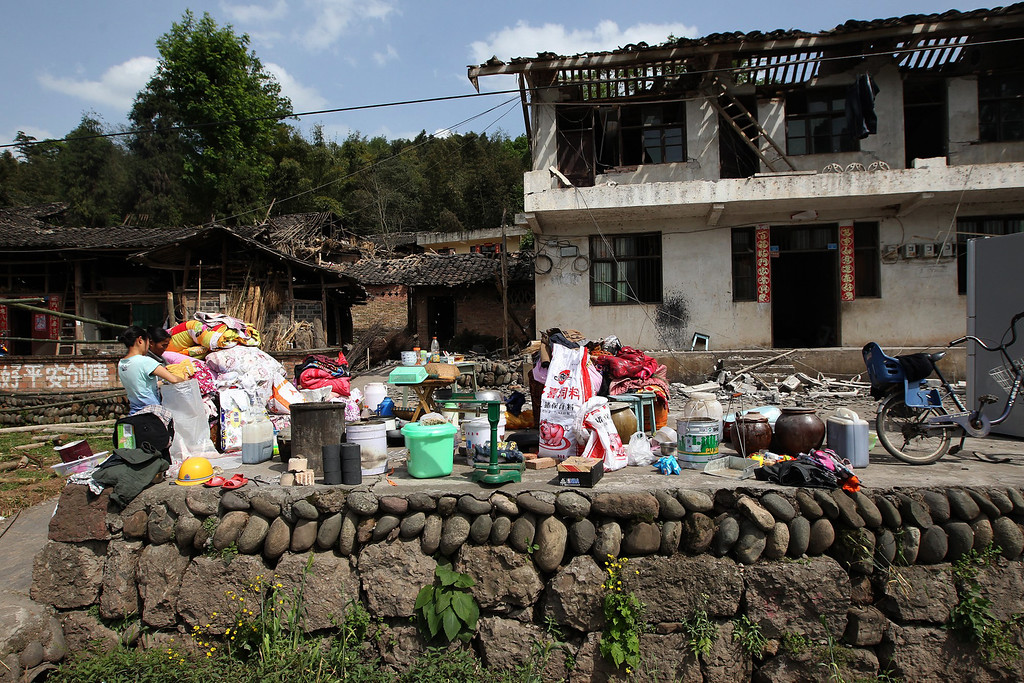. Residents stay outside damaged houses in Longmen township, an area very close to the epicenter of a shallow earthquake at magnitude 7.0 that hit the city of Ya\'an, southwest China\'s Sichuan province on April 20, 2013. More than 100 people were killed and 3,000 injured when a strong earthquake shook southwest China on April 20, wrecking homes and triggering landslides in an area devastated by a major tremor in 2008. AFP PHOTOSTR/AFP/Getty Images