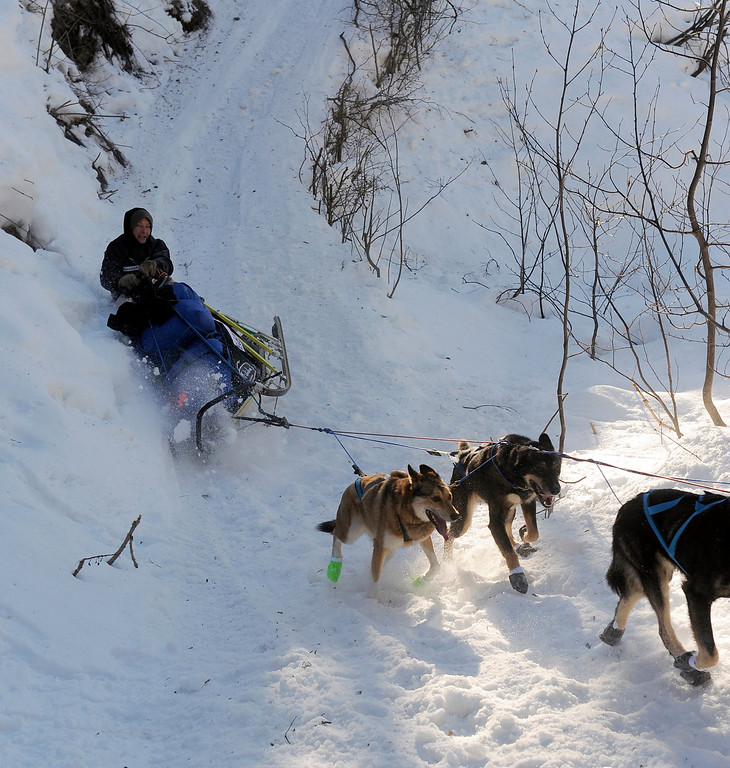 . In this March 3, 2014 photo, Ralph Johannessen, of Dagali, Norway, rolls his sled as he comes down the steps onto the Happy River between the Finger Lake and Rainy Pass checkpoints heading to Puntilla Lake, Alaska, during the 2014 Iditarod Trail Sled Dog Race. (AP Photo/The Anchorage Daily News, Bob Hallinen)