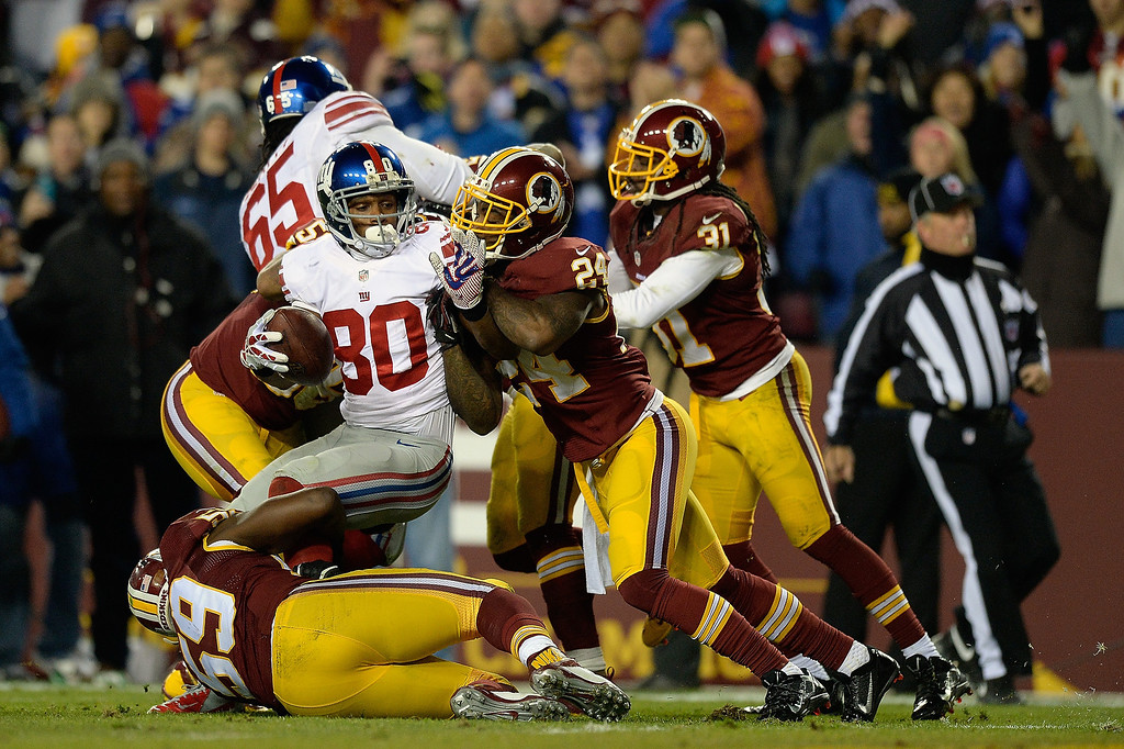 . LANDOVER, MD - DECEMBER 01:  Victor Cruz #80 of the New York Giants is stopped short of the endzone in the second half by Bacarri Rambo #24 and London Fletcher #59 of the Washington Redskins during an NFL game at FedExField on December 1, 2013 in Landover, Maryland.  (Photo by Patrick McDermott/Getty Images)