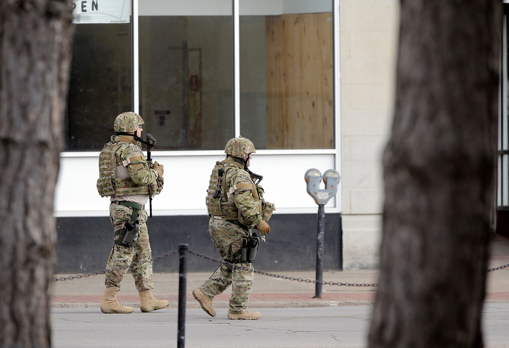 . Law enforcement officers walk along Main Street while searching for a suspect in two shootings Wednesday, March 13, 2013, in Herkimer, N.Y.  (AP Photo/Mike Groll)