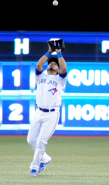 . Toronto Blue Jays\' Maicer Izturis catches a fly ball to end the sixth inning against the Colorado Rockies during their MLB interleague game in Toronto June 17, 2013.   REUTERS/Jon Blacker