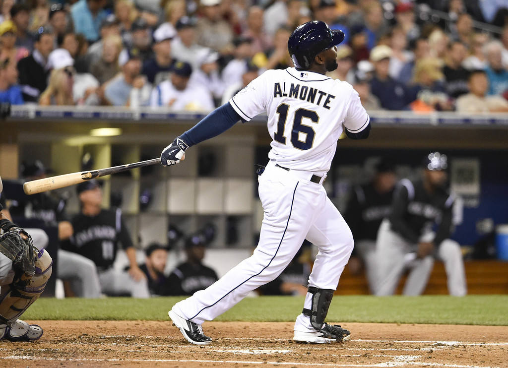 . SAN DIEGO, CA - AUGUST 12:  Abraham Almonte #16 of the San Diego Padres hits a sacrifice fly ball during the fourth inning of a baseball game against the Colorado Rockies at Petco Park August, 12, 2014 in San Diego, California.  (Photo by Denis Poroy/Getty Images)