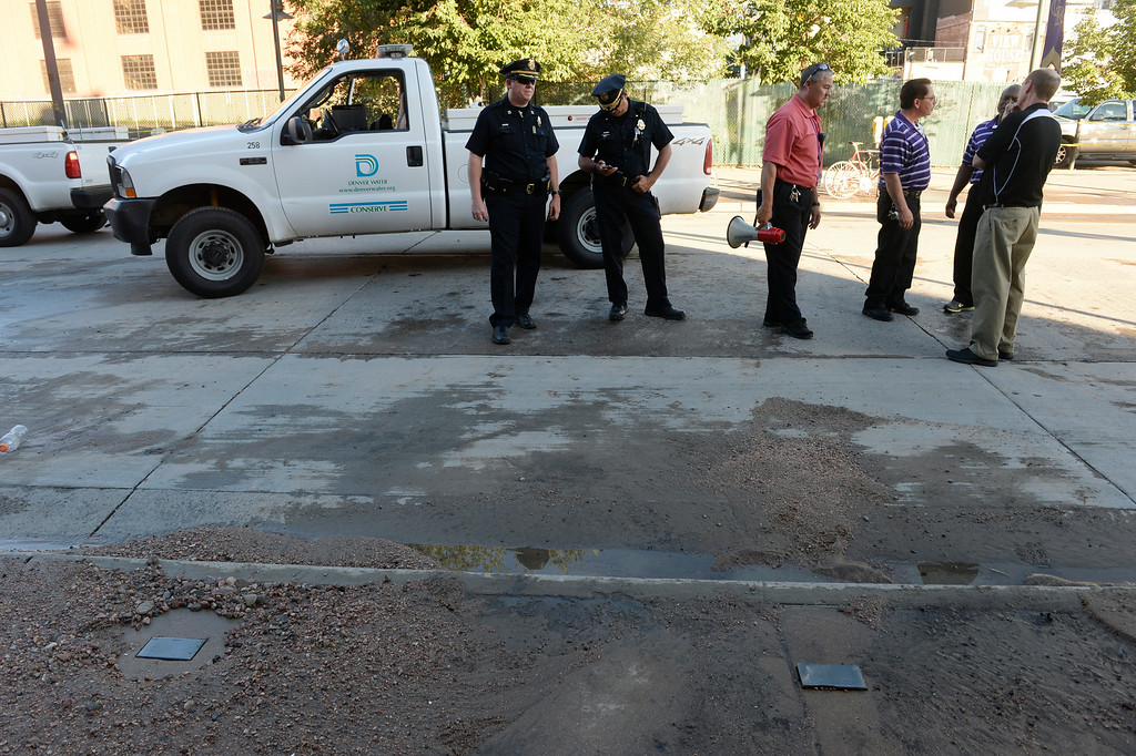 . DENVER, CO. - AUGUST 16:  Denver Police officers and Colorado Rockies officials stand along Blake St. in front of Coors Field Saturday evening, August 16, 2014. The game scheduled against the Cincinnati Reds was cancelled due to a water main break along Blake St, cutting off water supply to the stadium. (Photo By Andy Cross / The Denver Post)