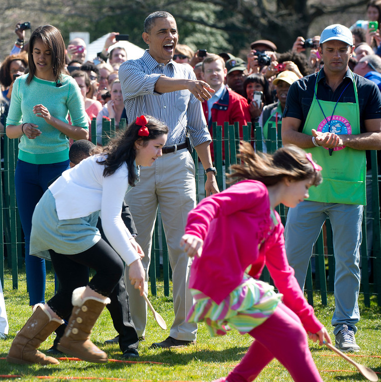 . US President Barack Obama cheers as children race to roll eggs as they participate in the White House Easter Egg Roll on the South Lawn of the White House in Washington, DC, April 1, 2013. Obama hosts the annual event, featuring live music, sports courts, cooking stations, storytelling and Easter egg rolling. AFP PHOTO / Saul LOEB/AFP/Getty Images