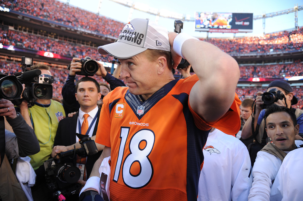 . Broncos quarterback Peyton Manning (18) puts on his AFC Championship cap after the Broncos beat the New England Patriots in the AFC Championship game at Sports Authority Field at Mile High in Denver on January 19, 2014. (Photo by Hyoung Chang/The Denver Post)