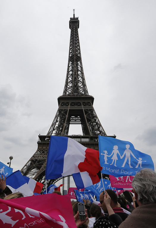 ". Supporters of the anti-gay marriage movement ""La Manif Pour Tous\"" (Demonstration for all) wave flags in front of the Eiffel Tower during a mass protest on May 26, 2013 in Paris against a gay marriage law. France on May 18 became the 14th country to legalize same-sex marriage after President Francois Hollande signed the measure into law following months of bitter debate and demonstrations.  FRANCOIS GUILLOT/AFP/Getty Images"