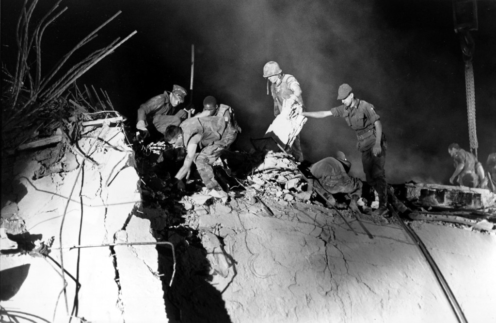 """. In this Monday, Oct. 24, 1983, file photo, U.S. Marines and an Italian soldier, right, dig through the rubble of the battalion headquarters, in Beirut, Lebanon, working around the clock searching for victims of the suicide truck bomb attack against the U.S. Marine barracks on Oct. 23, 1983. A massive, four-story building that had withstood air strikes and artillery was now reduced to a mountain of rubble and enormous chunks of concrete. Watching crews remove wreckage, I thought, \""""My God. How did anyone survive?\"""" AP\'s Cairo bureau chief at the time, Robert H. Reid recounts of the Oct. 23, 1983 bombing of the U.S. Marines barracks in Beirut that killed 241 Americans, one of the U.S.\'s first experiences with a Mideast suicide attack. (AP Photo/Bill Foley, File)"""