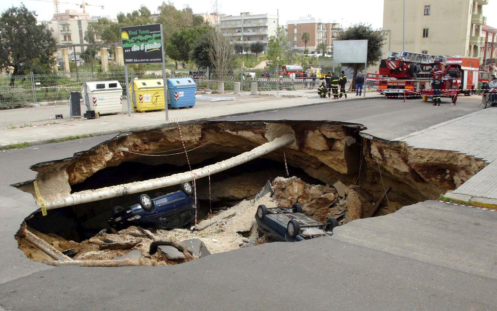 . Cars lie in a sinkhole, caused when a road collapsed into an underground cave system, in the southern Italian town of Gallipoli March 30, 2007. There were no injuries in the overnight incident, according to local police.  REUTERS/Fabio Serino