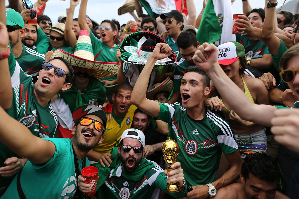 . Mexico soccer fans celebrate their team\'s 1-0 victory over Cameroon at a World Cup match, inside the FIFA Fan fest area on Copacabana beach in Rio de Janeiro, Brazil, Friday, June 13, 2014. (AP Photo/Leo Correa)