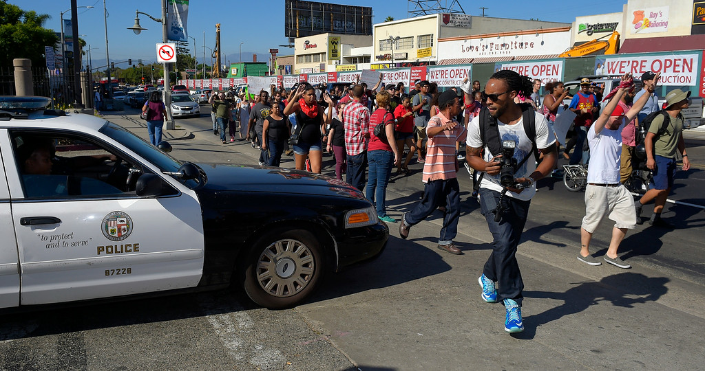 . Protesters pass by a Los Angeles Police Department car as they walk up Crenshaw Blvd. to protest the shooting of an unarmed man in Ferguson, Mo.,  and other victims of police shootings, Thursday, Aug. 14, 2014, in Los Angeles. (AP Photo/Mark J. Terrill)