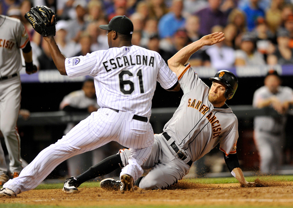 . San Francisco Giants\' Hunter Pence scores as Colorado Rockies relief pitcher Edgmer Escalona (61) covers home during the seventh inning of a baseball game on Friday, May 17, 2013, in Denver. (AP Photo/Jack Dempsey)