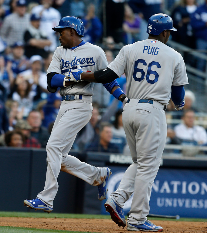 . Los Angeles Dodgers\' Dee Gordon is met by Yasiel Puig after scoring against the San Diego Padres on a single by Carl Crawford in the fifth inning of the opening game of Major League baseball in the United States Sunday, March 30, 2014, in San Diego.  (AP Photo/Lenny Ignelzi)