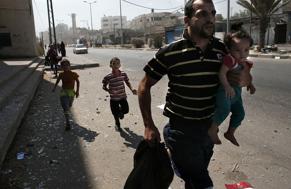 . A Palestinian man carrying his daughter runs with his sons, from their neighbourhood following six Israeli air strikes on homes in Gaza City on August 23, 2014. Israeli warplanes pounded Gaza, killing five Palestinians from the same family, two of them children, as the war between Israel and Hamas entered a 47th day. THOMAS COEX/AFP/Getty Images