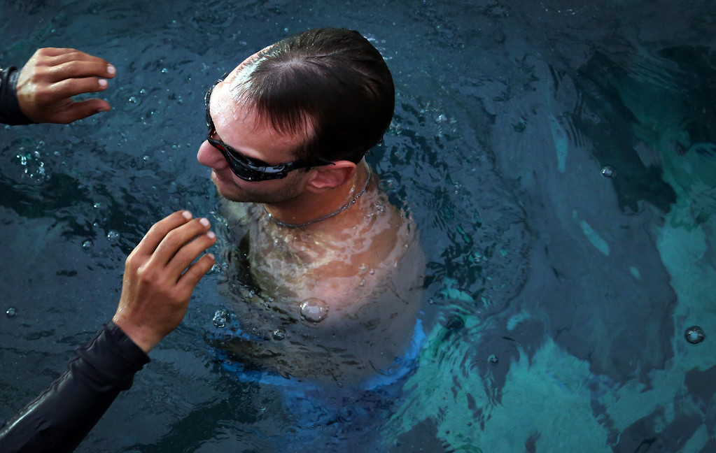 """. Nick Vujicic gets a helping hand from a life guard to empty water from his goggles after diving into an acrylic enclosure to keep him safe while diving among sharks Thursday, Sept. 5, 2013 in Singapore. Vujicic, a Serbian Australian evangelist and motivational speaker born with tetra-amelia syndrome, a rare disorder characterized by the absence of all four limbs, is in the city-state to give a motivational talk and was visiting \""""The Shark Encounter at Marine Life Park\"""" at one of Singapore\'s main tourist attractions in Resorts World Sentosa. (AP Photo/Wong Maye-E)"""