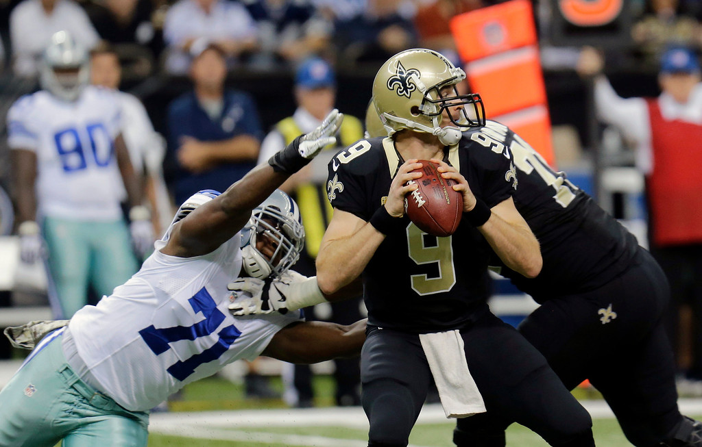 . New Orleans Saints quarterback Drew Brees (9) passes under pressure from Dallas Cowboys defensive end Everette Brown (71) in the first half of an NFL football game in New Orleans, Sunday, Nov. 10, 2013. (AP Photo/Bill Haber)