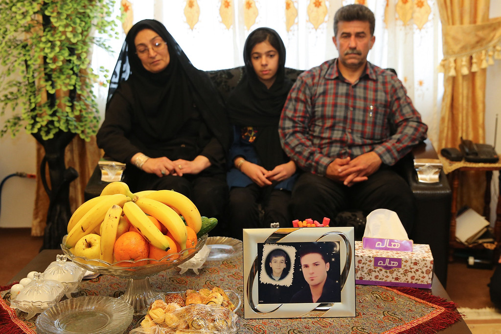 . Samereh Alinejad (L), Abdolghani Hosseinzadeh (R) and their daughter sit on a sofa in front of a picture of their son Abdolah Hosseinzadeh who was killed by a fellow Iranian, Balal, in a street fight with a knife in 2007, after they spared the life of their son\'s convicted murderer during his execution ceremony in the northern city of Nowshahr on April 15, 2014. AFP PHOTO/ARASH KHAMOOSHI/AFP/Getty Images