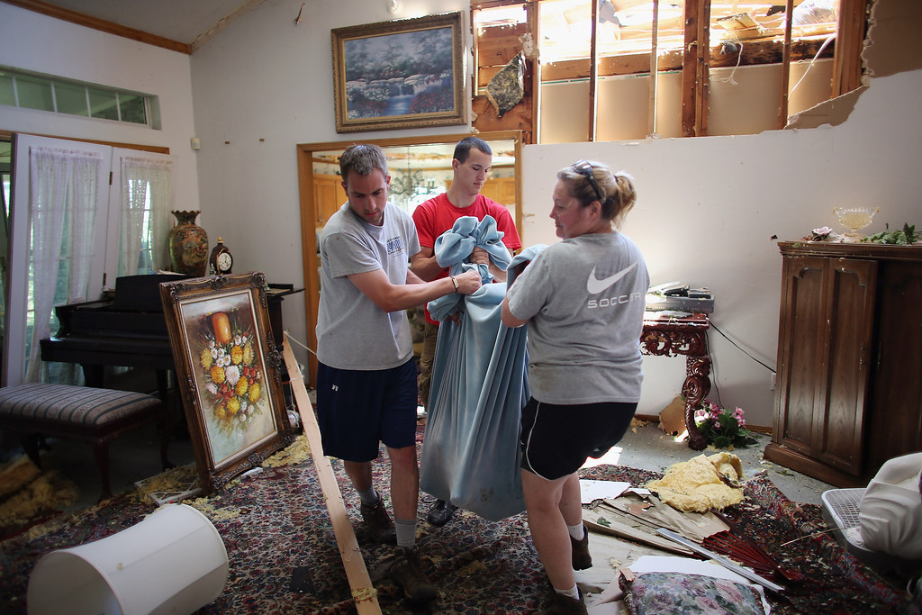 . EL RENO, OK - JUNE 01: (L-R) Josh Hill, Dylan Lager and Holly Mais carry an injured dog out of a home damaged by a passing tornado on June 1, 2013 in El Reno, Oklahoma. The tornado ripped through the area killing at least nine people, injuring many others and destroying homes and buildings.  (Photo by Joe Raedle/Getty Images)