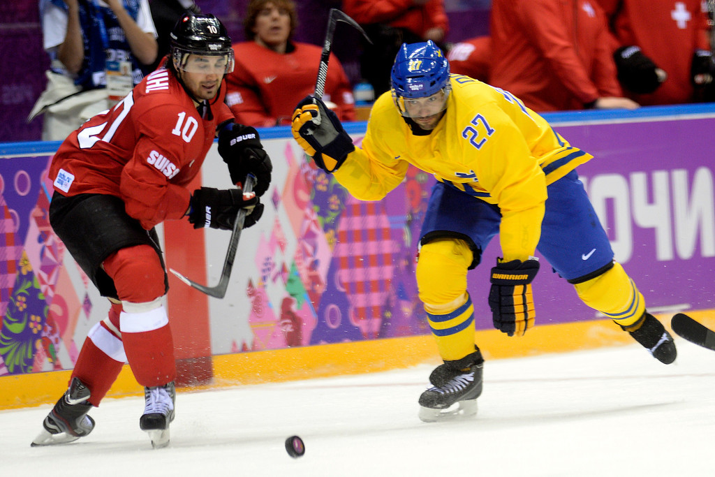 . Sweden\'s Johnny Oduya and Switzerland\'s Andres Ambugl race to the puck during the third period of Sweden\'s 1-0 preliminary round group C win at Bolshoy Arena. Sochi 2014 Winter Olympics on Friday, February 14, 2014. (Photo by AAron Ontiveroz/The Denver Post)