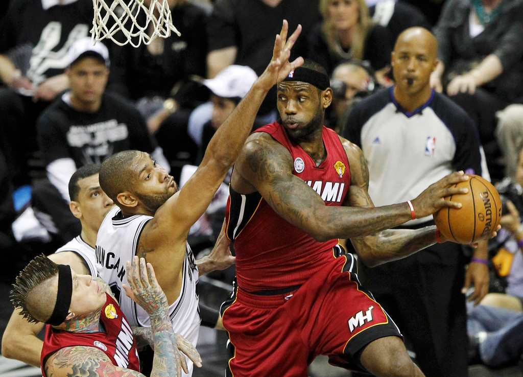 . Miami Heat\'s LeBron James (R) is guarded by San Antonio Spurs\' Tim Duncan in the first half during Game 3 of their NBA Finals basketball series in San Antonio, Texas June 11, 2013. REUTERS/Mike Stone