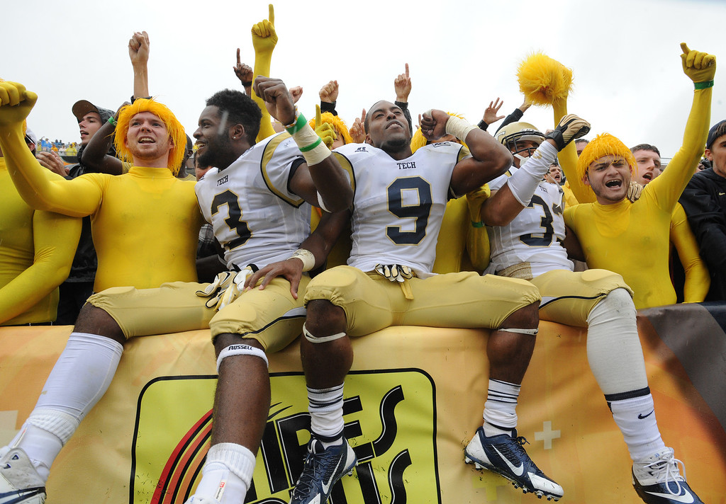 . Georgia Tech\'s Dennis Andrews (3),  Tony Zenon (9) and Beau Hankins (33) celebrate with fans after their 28-20 win over North Carolina in an NCAA college football game at Bobby Dodd Stadium on Saturday, Sept. 21, 2013, in Atlanta, (AP Photo/Atlanta Journal-Constitution, Johnny Crawford)