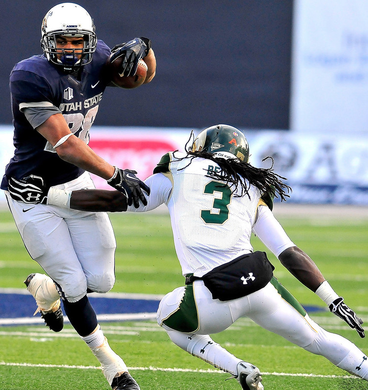 . Utah State\'s Joey DeMartino, left, breaks a tackle from Colorado State\'s Shaq Bell during an NCAA college football game, Saturday, Nov. 23, 2013, in Logan, Utah. Utah State won 13-0. (AP Photo/Herald Journal, John Zsiray)