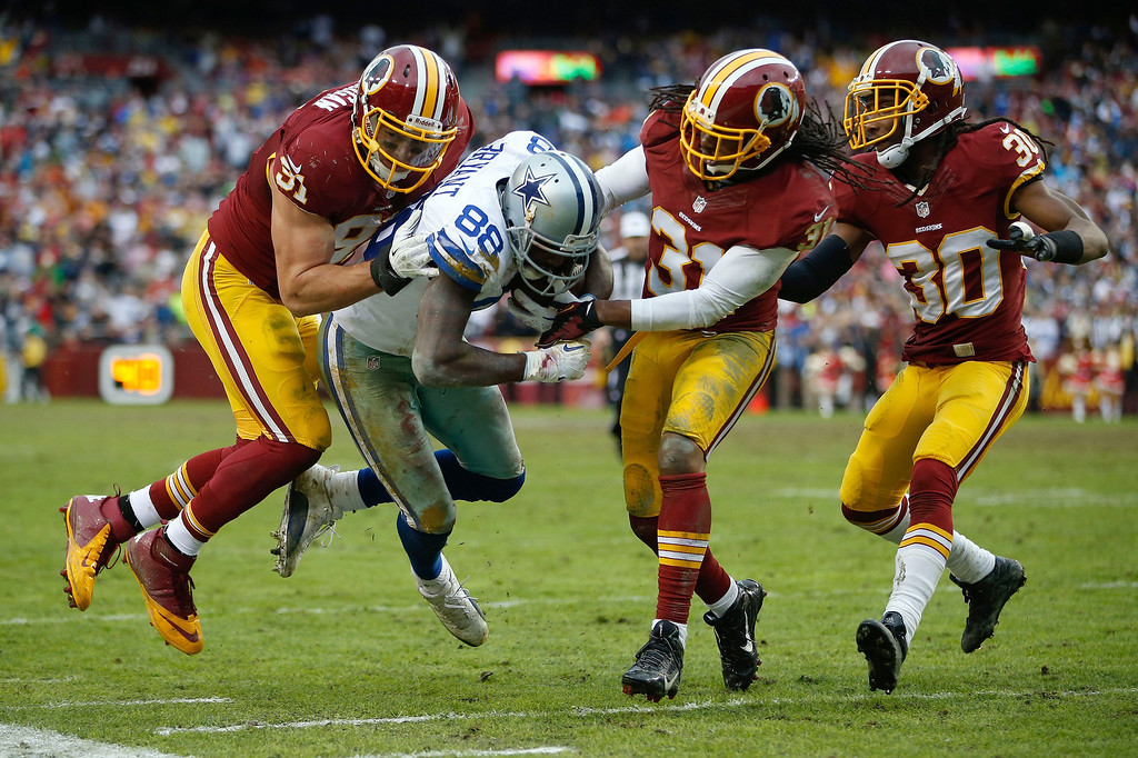 . Dallas Cowboys wide receiver Dez Bryant is knocked up of bounds short of the goal line by Washington Redskins outside linebacker Ryan Kerrigan, left, strong safety Brandon Meriweather (31) and free safety E.J. Biggers (30) during the second half of an NFL football game in Landover, Md., Sunday, Dec. 22, 2013. The Cowboys defeated the Redskins 24-23. (AP Photo/Evan Vucci)