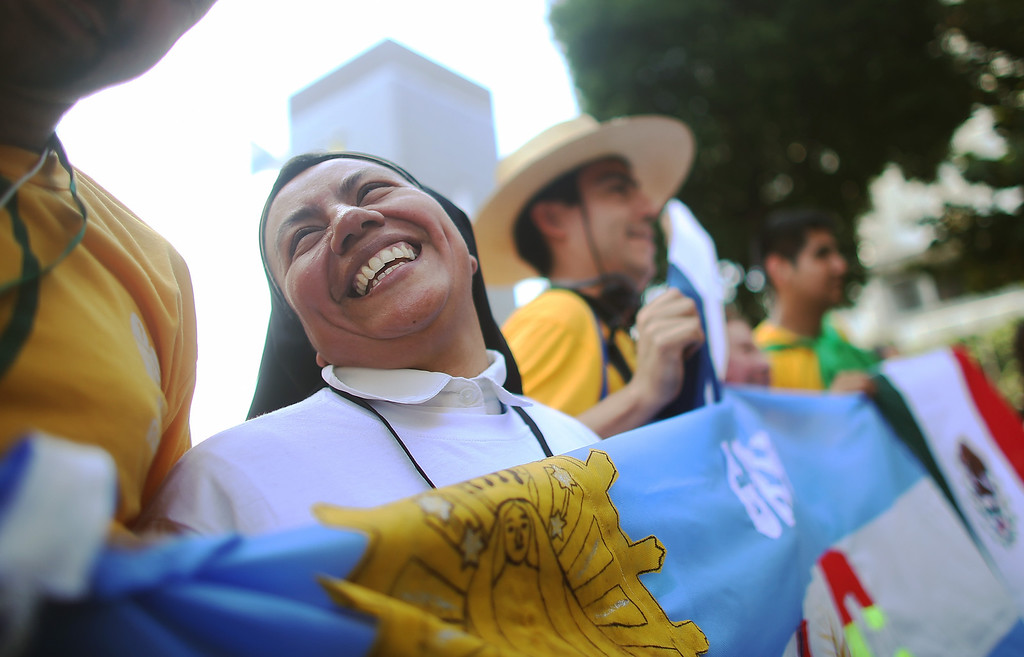 . Nun Concepcion Hernandez, originally from Mexico, holds an Argentinian flag while awaiting the arrival of Pope Francis outside the Metropolitan Cathedral on July 22, 2013 in Rio de Janeiro, Brazil. Hernandez is currently a Catholic missionary in Argentina. More than 1.5 million pilgrims are expected to join Pope Francis for his visit to the Catholic Church\'s World Youth Day celebrations. Pope Francis is scheduled to visit Brazil from July 22 to 28.  (Photo by Mario Tama/Getty Images)