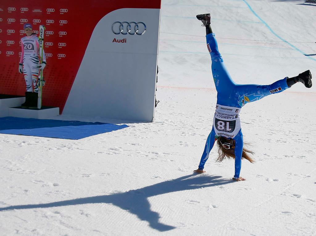 . Germany\'s Maria Hoefl-Riesch (L) watches as Slovenia\'s Tina Maze arrives for the winners presentation of the women\'s Alpine Skiing World Cup Downhill race in Garmisch-Partenkirchen March 2, 2013.  REUTERS/Michael Dalder