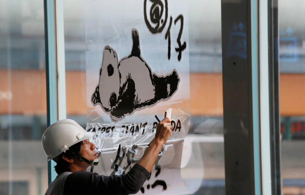 . A worker applies a decal on a glass advertising Taiwan\'s six-month-old panda cub Yuan Zai\'s first public viewing at the Taipei Zoo in Taipei, Taiwan, Monday, Jan. 6, 2014. The panda cub, whose parents were gifts from China to Taiwan in 2008, was shown to the public for the first time Monday, as long lines of visitors of all ages queued up at the zoo. (AP Photo/Wally Santana)
