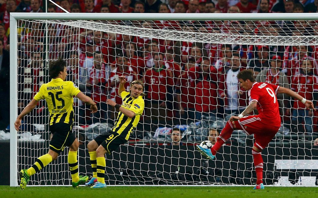. Bayern Munich\'s Mario Mandzukic score a goal past Borussia Dortmund\'s Mats Hummels (L) and Marcel Schmelzer (C) during their Champions League final soccer match at Wembley stadium in London May 25, 2013.         REUTERS/Michael Dalder