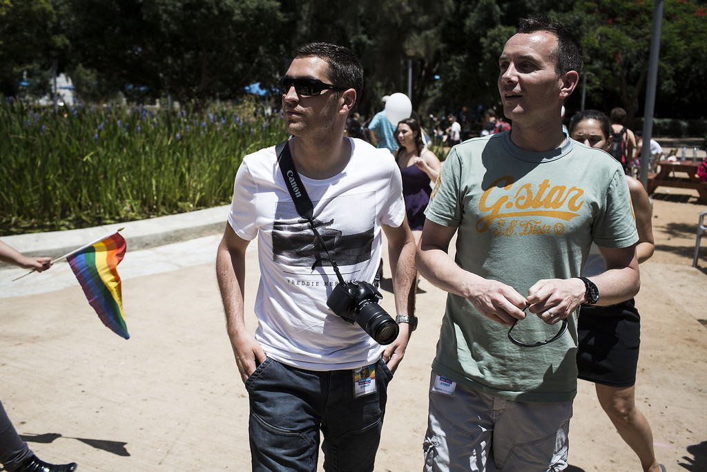. The first French married gay couple, Vincent Autin (R) and his partner Bruno Boileau walk in the park during the annual Tel Aviv Gay Pride parade on June 7, 2013 in Tel Aviv, Israel. (Photo by Ilia Yefimovich/Getty Images)