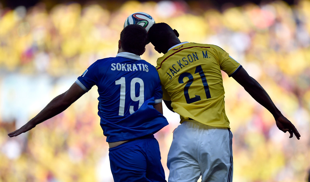 . Greece\'s Sokratis Papastathopoulos, left,  heads the ball against Colombia\'s Jackson Martinez during the group C World Cup soccer match between Colombia and Greece at the Mineirao Stadium in Belo Horizonte, Brazil, Saturday, June 14, 2014.  Colombia won 3-0. (AP Photo/Martin Meissner)