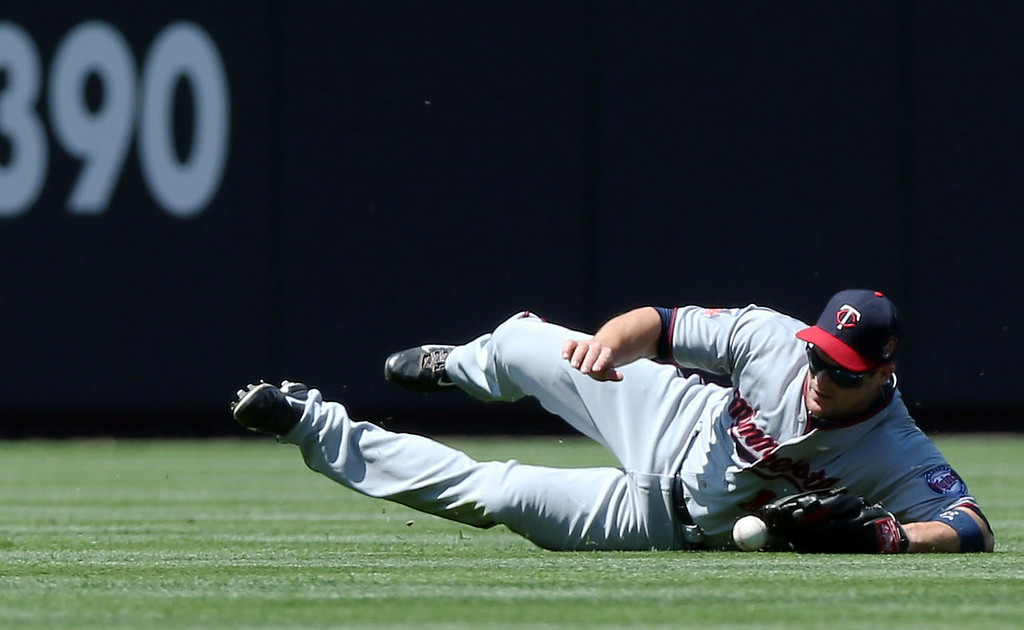 . Minnesota Twins left fielder Josh Willingham dives but misses a ball that went for a double  by Colorado Rockies\' Nolan Arenado in the first inning of an interleague baseball game in Denver on Sunday, July 13, 2014. (AP Photo/David Zalubowski)