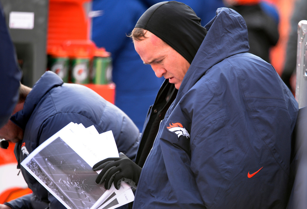 . Denver Broncos quarterback Peyton Manning (18) studies on the sidelines during the first half.  The Denver Broncos vs. the Tennessee Titans at Sports Authority Field at Mile High in Denver on December 8, 2013. (Photo by Tim Rasmussen/The Denver Post)