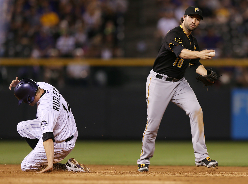 . Pittsburgh Pirates second baseman Neil Walker, right, holds off from throwing the ball after forcing out Colorado Rockies\' Josh Rutledge, left, at second base in the eighth inning of the Rockies\' 8-1 victory in a baseball game in Denver, Saturday, July 26, 2014. (AP Photo/David Zalubowski)