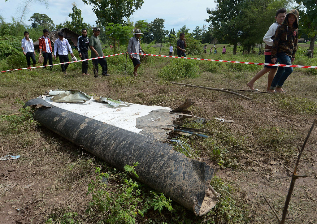 . People walk past pieces of a Lao Airlines plane after it crashed into the Mekong river near Pakse town, on October 17, 2013.   AFP PHOTO / PORNCHAI  KITTIWONGSAKUL/AFP/Getty Images