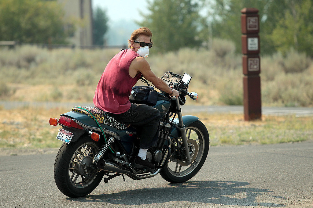 . Chris Sanford uses a mask to help block out smoke from the Beaver Creek Fire during a ride on Sunday, Aug. 18, 2013, in Hailey, Idaho. Evacuations are still in place for parts of the Wood River Valley from the 92, 754 acre fire. (AP Photo/Times-News, Ashley Smith)
